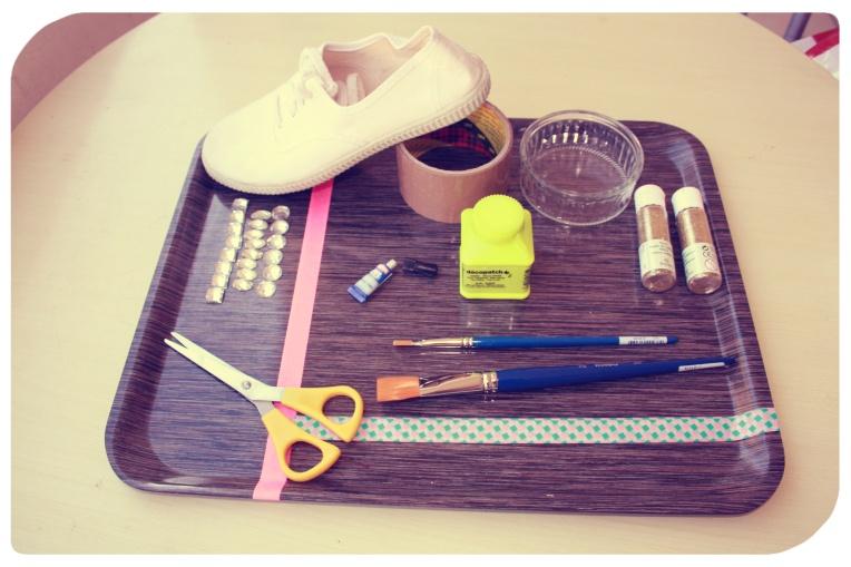 Pour ce DIY il vous faut : - Des chaussures blanches en tissu - Du Scotch gros format et petit format - Des strass - Une paire de ciseaux - 1 pinceau fin - 1 pinceau épais - 1 tube de paillettes  - De la colle pour loisirs créatifs (Vernis colle qui résisite à l'eau) - Un récipient - De la glue